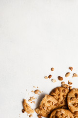 Culinary background of wholegrain cookies with peanuts. Delicious homemade sweets on white table, close up top view with free space