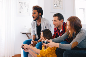 Group of happy young friends playing video games at home.
