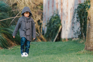 Young boy playing football / soccer in his garden
