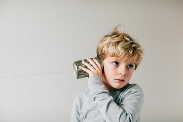 disinterested boy listening through a tin can phone