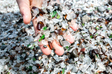 Womans hands holding sea glass  with sea glass in background