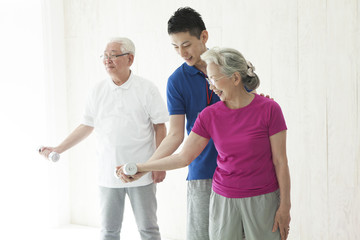 An elderly couple training a dumbbell while being told by a trainer