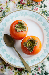 Two persimmons on a plate