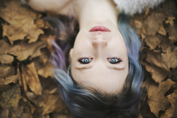 Portrait of a beautiful young woman lying down in autumn leaves