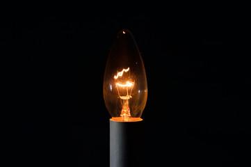Metalowy żarnik w żarówce świecące w ciemności.