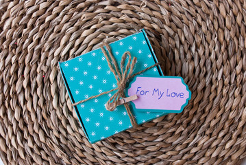 Packaged present with label for my love on straw support. Christmas or valentine background with care.