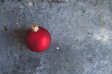 bright red Christmas bauble sits atop of a concrete textured background