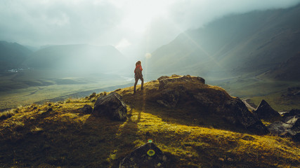 Hiker Young Woman With Backpack Rises To The Mountain Top Against Backdrop Of Sunset. Discovery Travel Destination Concept