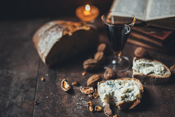 Slice of bread with blue cheese, wine, nuts and candle