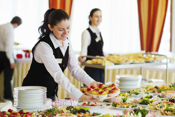 Restaurant waitress serving table with food