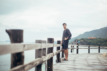 Landscape image of young man on wooden boardwalk by sea looking off into the distance