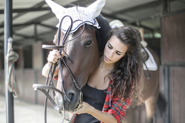 Girl preparing her horse for a competition
