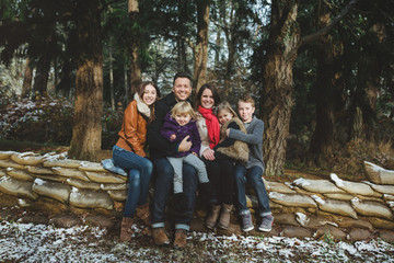 Happy young family posing cozy for portrait outside in winter