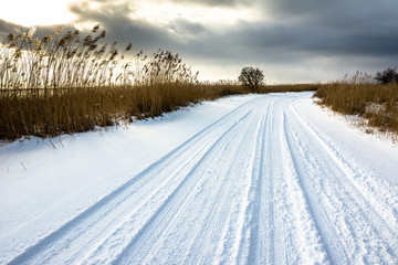 Snow on road, winter landscape with moody sky before sunset over lake