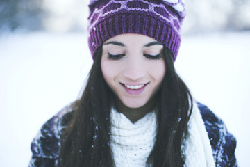 Portrait of a smiling young woman on a cold snowy day