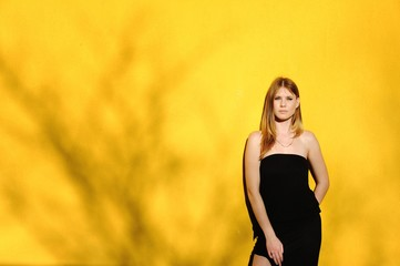 Girl next to a yellow wall