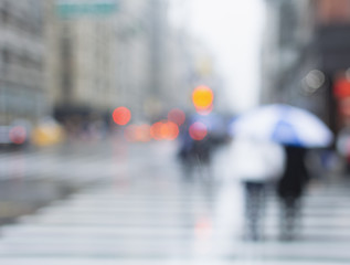 Blurred view of people crossing street on rainy day. New York City.