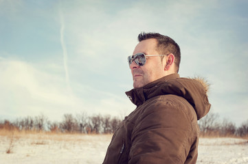 Man viewing the winter scenery wearing sunglasses with blue sky and trees in the background