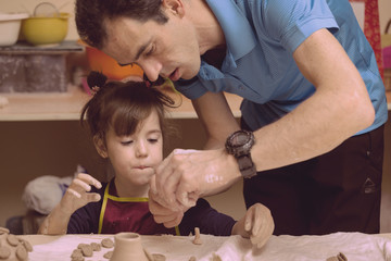 little girl in a pottery workshop
