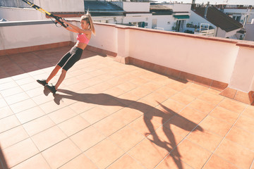 Slim girl working out with straps on rooftop.