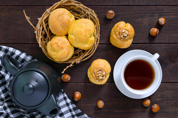 Air profiteroles filled with caramel cream with nuts, tea cup, teapot on a dark wooden background. Top view.