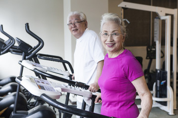 Elderly couple enjoying running machines together
