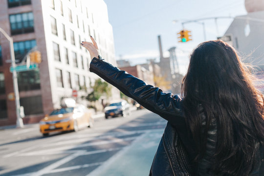 Attractive woman calling a taxi in New York City