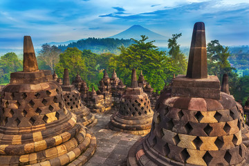 Candi Borobudur in the background of rainforest, morning mist and Sumbing Mountain. Candi Borobudur, Yogyakarta, Jawa, Indonesia.