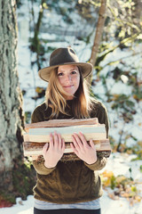 Portrait of a beautiful young woman holding a small pile of firewood