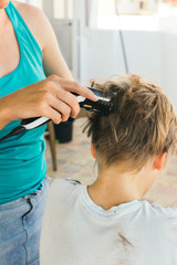 Mother cutting her son's hair with electric trimmer on the terrace