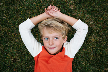 overhead portrait of a boy lying in the grass