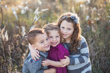 Blue-eyed smiling siblings hug in natural field