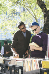 Young Gay Men Couple Browsing at Outdoor Used Books Sale at Manhattan's Central Park in New York