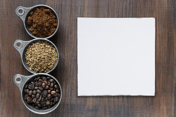 Different types of coffee and paper cadd on a wooden background