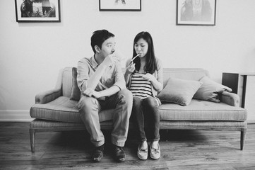 Asian couple sitting on couch on a date at a coffee shop