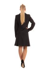 Frau mit langen blonden Haaren im Kleid von hinten freigestelltes Foto