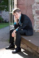 Junge sitzt gelangweilt im Anzug auf Mauer