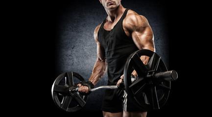 Młody seksowny bodybuilder z perfect ciałem robi ćwiczeniu z barbell na czarnym tle.