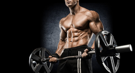 Young sexy bodybuilder with perfect body doing exercise with barbell on black background.