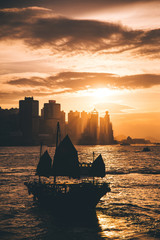 Silhouette boat and city of hong kong with sunset time.