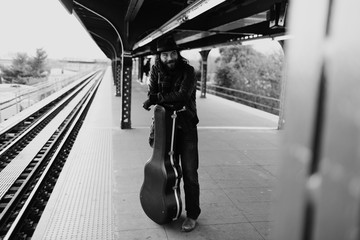 Young guitarist waits patiently on the NYC subway platform