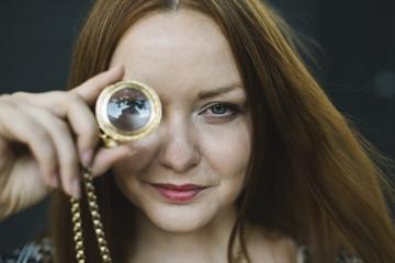 Woman looking through magnifying lens