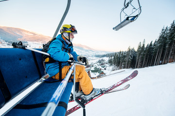 Shot of a skier sitting on a ski lift chair riding up to the top of the mountain copyspace winter extreme sports concept
