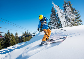 Shot of a professional freeride skier riding down in the Carpathians mountains at winter resort on a sunny day. Blue sky and winter forest on the background