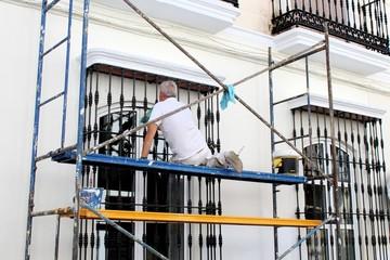 Maler auf einem Gerüst bei der Arbeit
