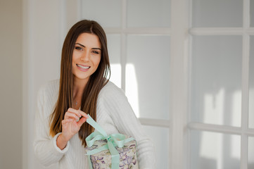 Smiling young sophisticated woman in elegant white interior home, holding a beautiful present round box, pulling the ribbon and opening the present, looking and smiling at camera.