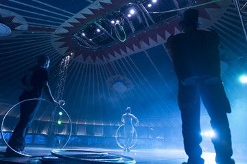 Circus peformer taking a bow with ringmaster and stage hand in foreground