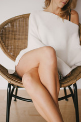 Young woman in knit sweater and bare skin legs sitting on chair with legs crossed