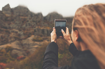 A young girl takes photos of a autumn mountain landscape. Foggy day