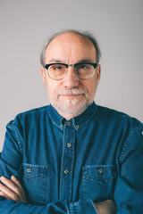 Portrait of a serious mature man wearing modern glasses and denim shirt.